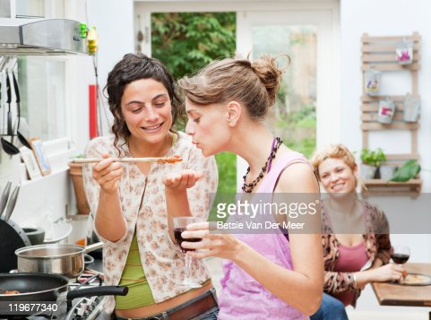woman feeding friend pastasauce to check taste.