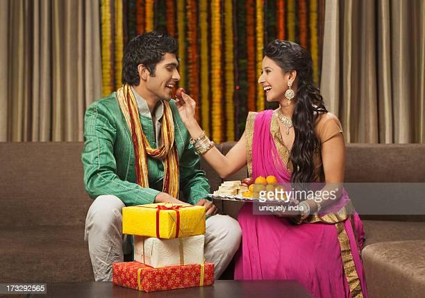 Woman feeding gulab jamun to her boyfriend on Diwali