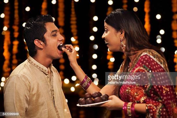 Woman feeding gulab jamun to her brother