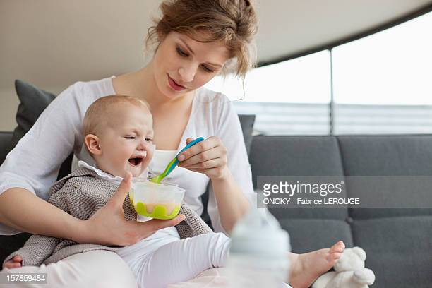 Woman feeding her daughter