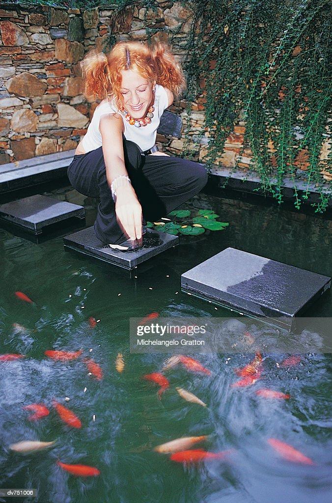 Woman Feeding her Koi Carp in a Garden Pond : Stock Photo