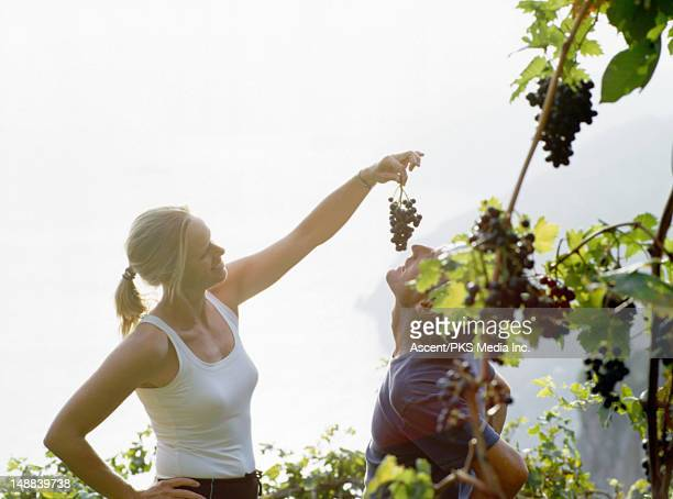 Woman feeding man a bunch of grapes.