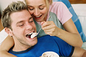 Woman feeding man ice cream
