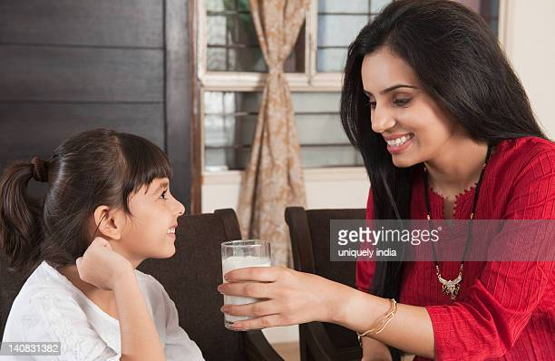 Woman feeding milk to her daughter