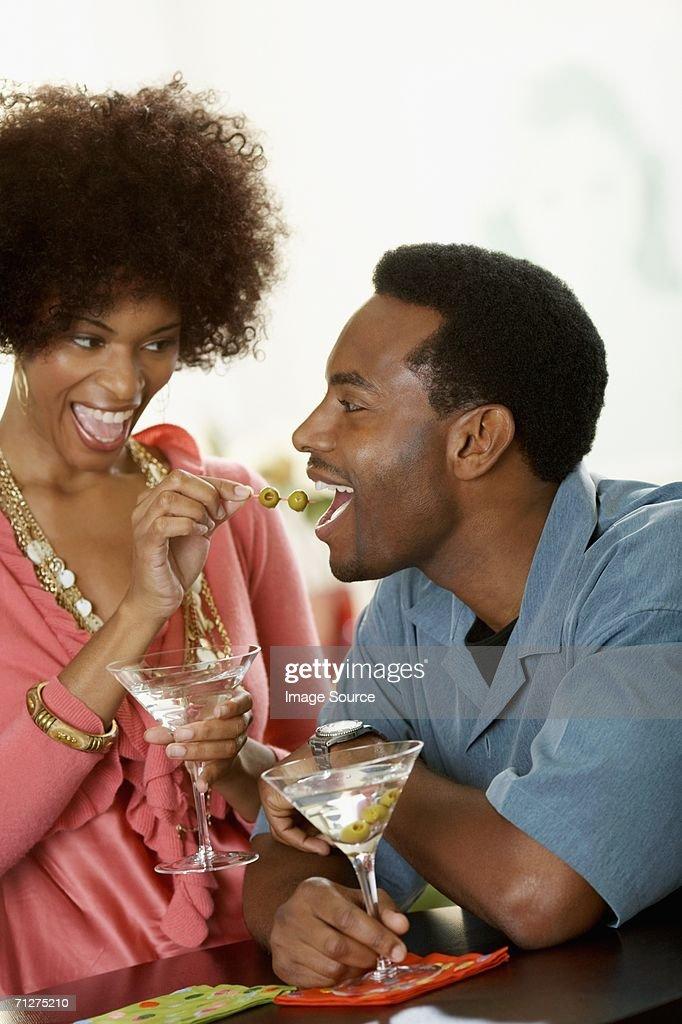 Woman feeding olives to man : Stock Photo