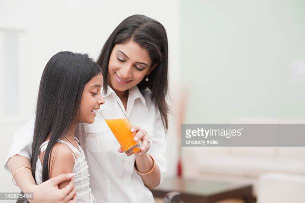 Woman feeding orange juice to her daughter