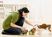 Woman feeding and petting puppy. Horizontally framed shot.