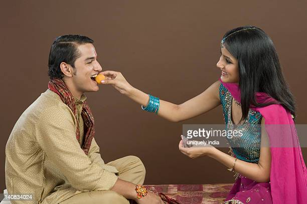 Woman feeding sweets to her brother at Raksha Bandhan festival