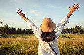 Woman rasie her hands and feel free by the nature of wide field