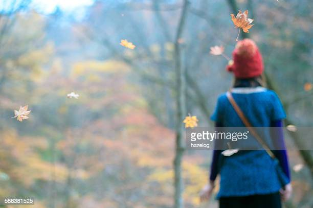 Woman feel the Autumn breeze with falling leave