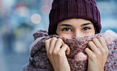 Winter portrait of young beautiful woman covering face with woolen scarf. Closeup of happy girl feeling cold outdoor in the city. Young woman holding scarf and looking at camera.'r