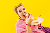 Feeling crazy. Woman with bright makeup feeling crazy while eating delicious sweet cake