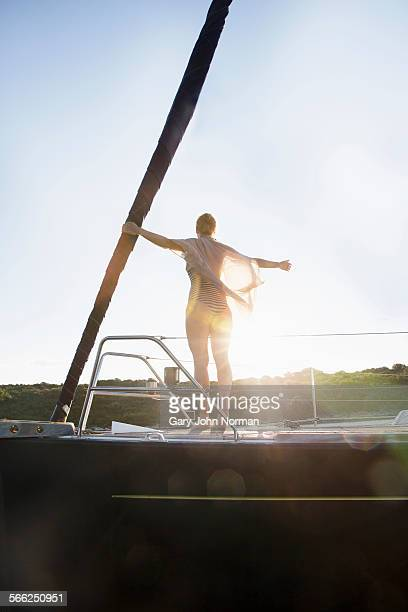 woman feeling the breeze on bow of sailing yacht.