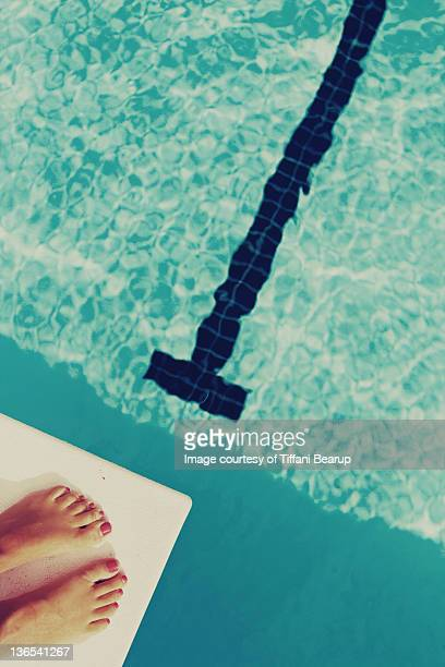 Woman feet on diving board looking down into pool