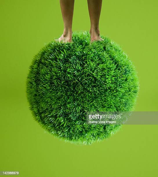 Woman feet over a grass globe