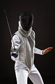 Portrait of Young woman fencer wearing mask and white fencing costume. Attacking pose. Dark Background
