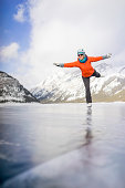 Woman figure skates across mountain pond