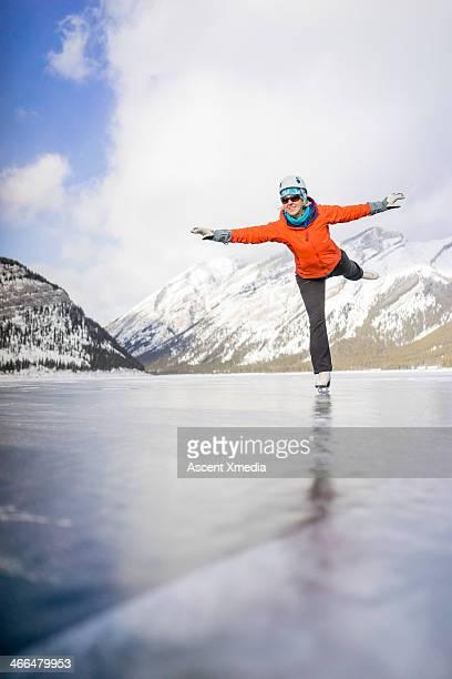 Woman figure skates across mountain pond