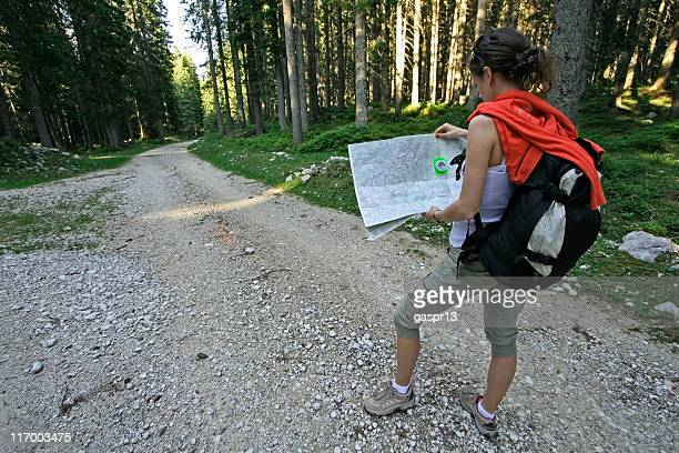 A woman figuring out where to go on her map in the woods