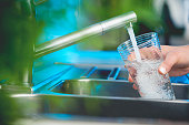 Woman filling a glass of water. She is using the faucet in the kitchen sink. There is a plant out of focus in the foreground. Close up with copy space.