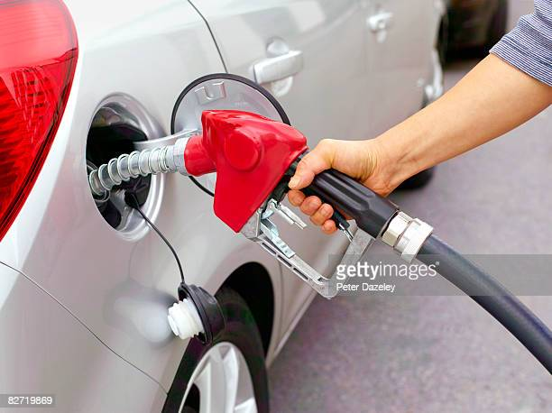 Woman filling car with leaded fuel.