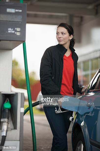 Woman filling car with petrol