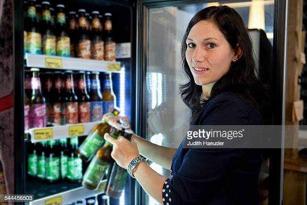 Woman filling fridge with drinks bottles in shop