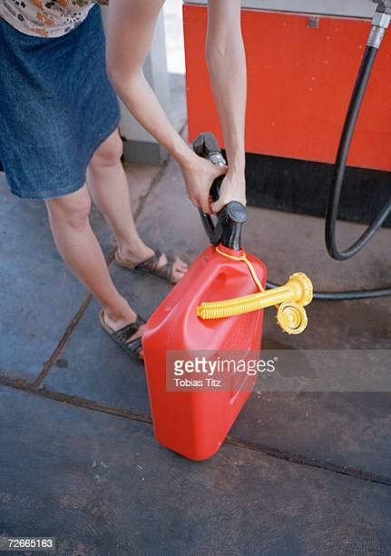 Woman filling gas can at gas  station,