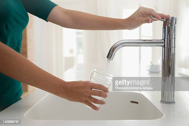 Woman filling glass of water at kitchen sink, cropped