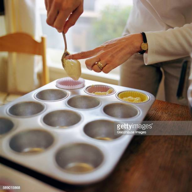 Woman Filling Muffin Tin with Batter