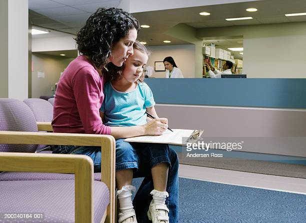 Woman filling out form, girl (3-5) on lap, in medical center
