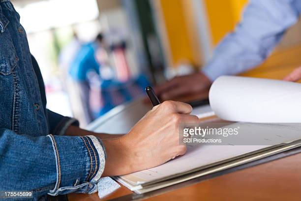 Frau beim Ausfüllen des Anmeldeformulars für eine Veranstaltung