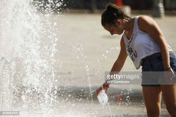 A woman fills a bottle with water in a fountain in Piazza San Carlo in Turin on August 5 2017 / AFP PHOTO / Marco BERTORELLO