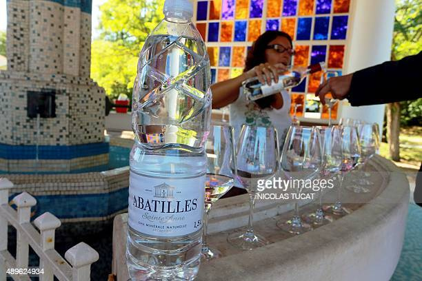 A woman fills a glass of wine of mineral water source 'Les Abatilles' in Arcachon during a tasting session on August 25 2015 Since 2013 Jean Merlaut...