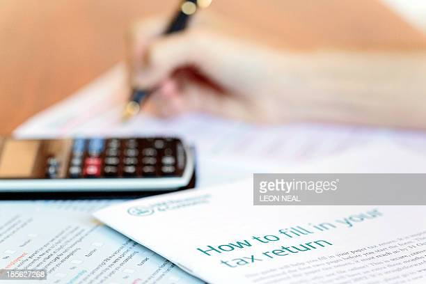 A woman fills a tax return form in London on November 6 2012 AFP PHOTO / LEON NEAL