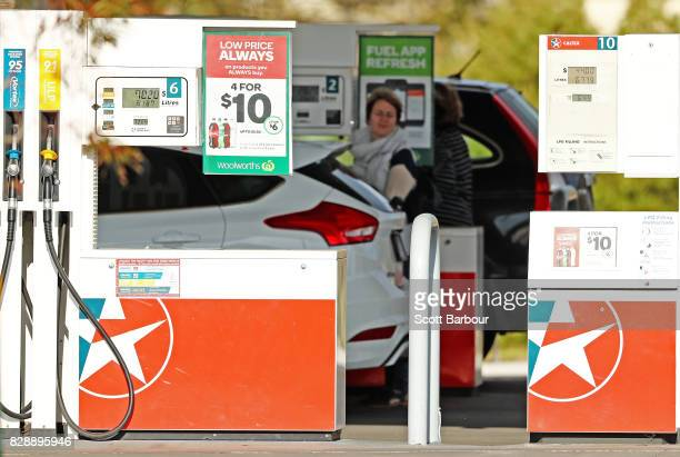 A woman fills her car up with petrol at a fuel dispenser at a Caltex Woolworths petrol station in Geelong on August 10 2017 in Melbourne Australia...