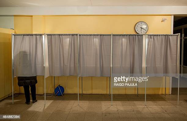 A woman fills out her ballot papers in a polling station during a parliamentary election in Tallinn on March 1 2015 Estonians voted in an election...