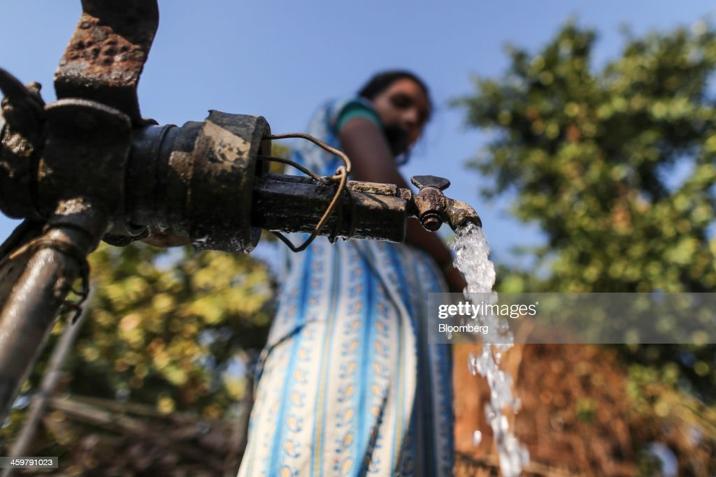 A woman fills pots with drinking water from a public water source in Kainad, Maharashtra, India, on Saturday, Dec. 21, 2013. The construction of 600,000 kilometers (373,000 miles) of country roads, addition of 327 million rural phone connections and a rise in literacy to record levels since Prime Minister Manmohan Singh took office in 2004 has helped double the growth rate of Indias food output. Photographer: Dhiraj Singh/Bloomberg via Getty Images