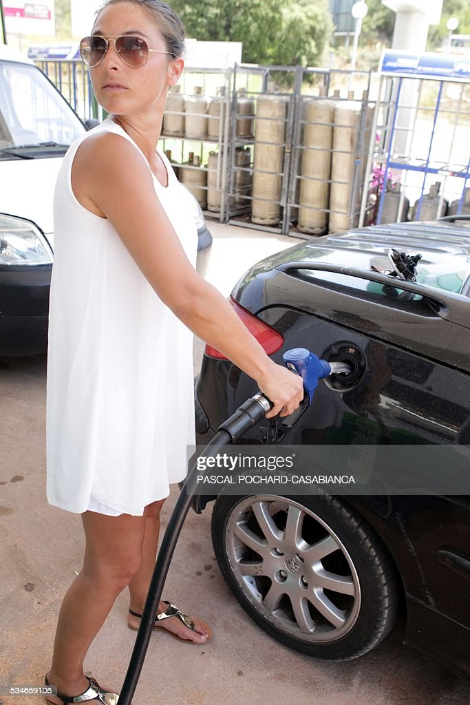 A woman fills up the tank of her car at one of the last gas stations not in shortage in the Ajaccio area on May 27, 2016 in Porticcio, on the French Mediterranean island of Corsica. / AFP / PASCAL