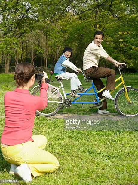 Woman filming husband and son on a tandem bike