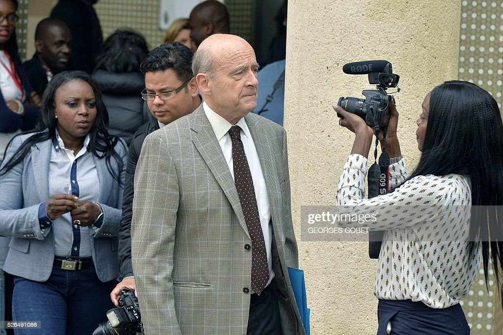 A woman films and interviews French mayor of Bordeaux and French candidate for the right-wing Les Republicains (The Republicans) presidential primary Alain Juppe, as he leaves the Joseph Wresinski room after the opening ceremony of the 4th edition of the Days of African diaspora on April 30, 2016 in Bordeaux. The event Days of African diaspora lasts two days during which debates about the role of diaspora and its contribution to the developement of the African continent will take place. / AFP / GEORGES