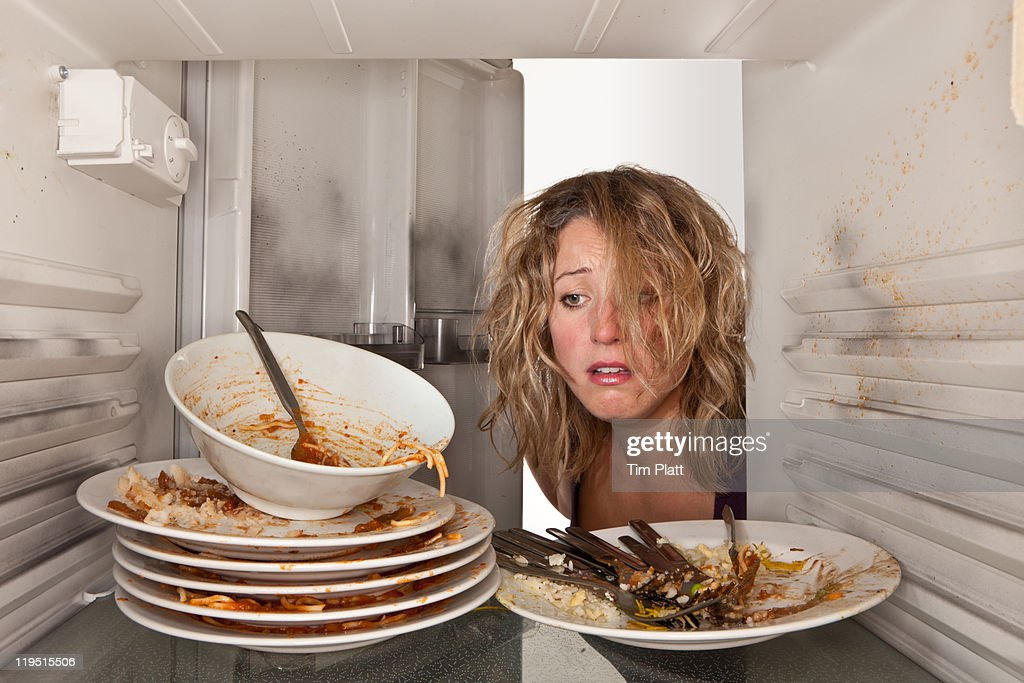 Woman finds dirty dishes in fridge : Stock Photo