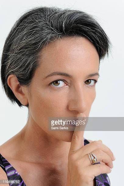 Woman finger on lips, looking at camera
