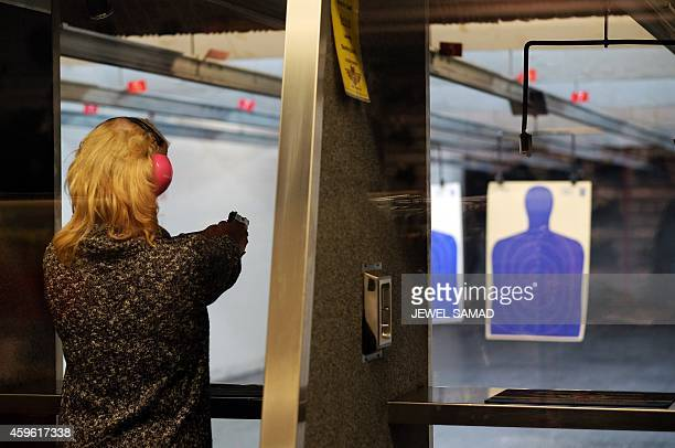 A woman fires a gun at the Ultimate Defense Firing Range and Training Center around 20 miles west of Ferguson in St Peters Missouri on November 26...