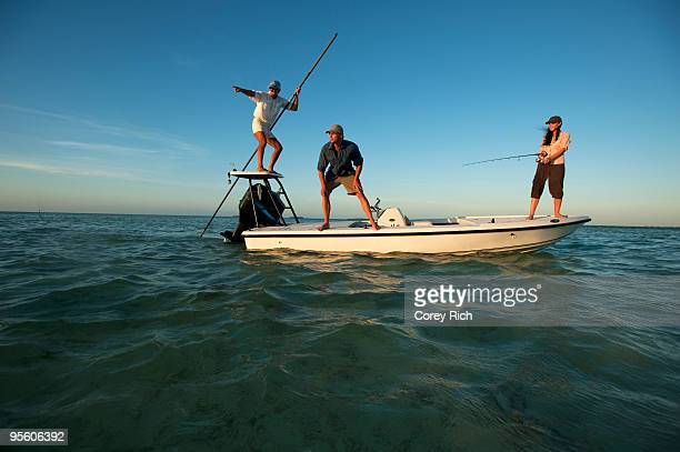 A woman fishes while one man watches and one man pilots the boat in Florida.