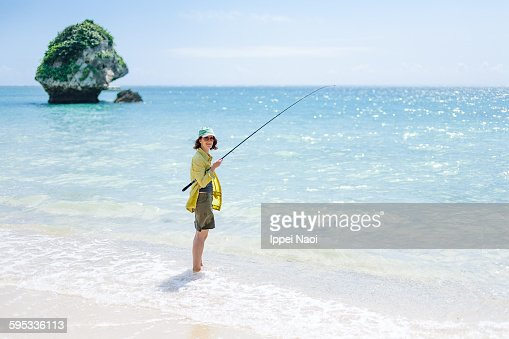 Woman fishing on tropical beach, Okinawa, Japan