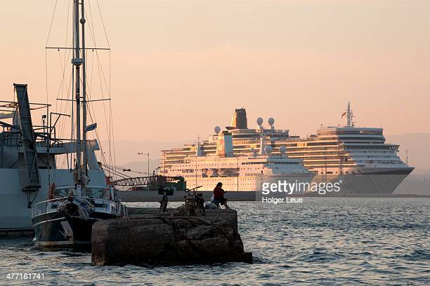 Woman fishing with cruise ships at pier