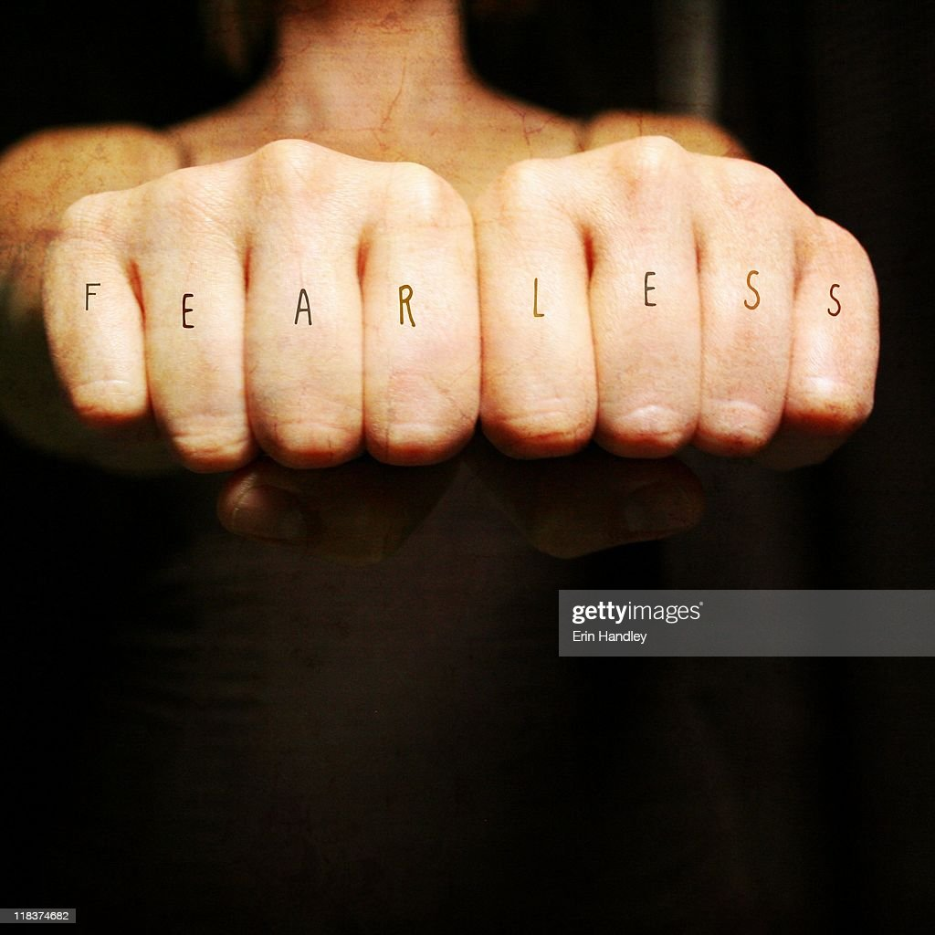 Woman fists with fearless across the knuckles : Stock Photo