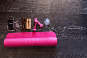 Top view image of jumping rope, smart phone, pink yoga mat and pink weights with a bottle of water on black wooden floor background. Equipment for fitness. Concept healthy lifestyle. Lots of copy spac