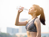 Woman fitness outdoor concept, young asian beautiful woman drinking water during workout, running, jogging, yoga at outdoor park, fresh, relax, happy feeling